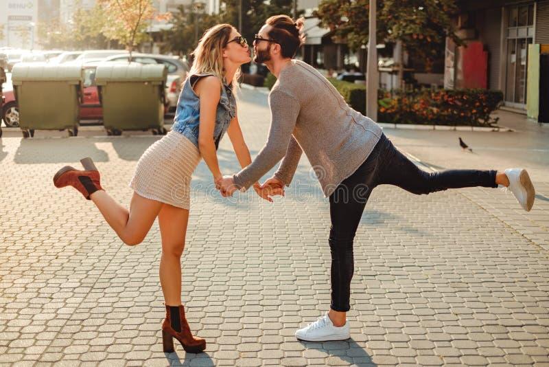 El besarse de los pares divertido en la acera imagenes de archivo