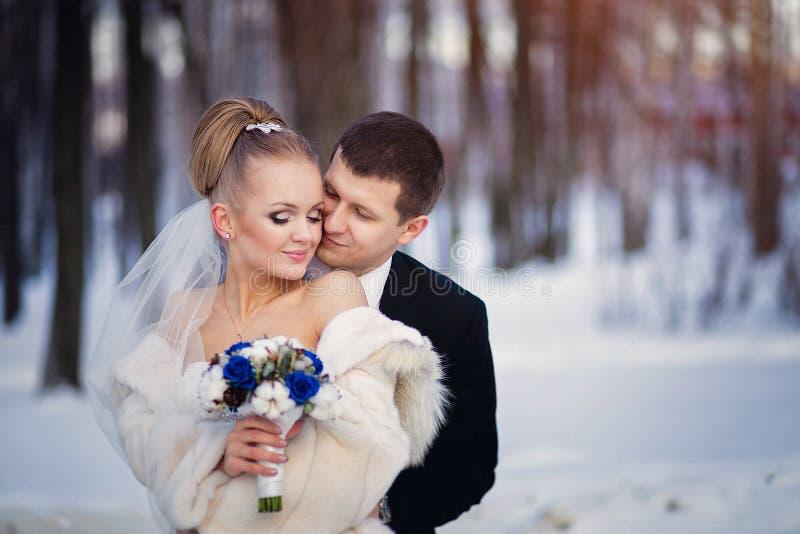 El besarse de novia y del novio de la boda y pares blandos cariñosos con el ramo de flores azules en el día nupcial del invierno fotos de archivo libres de regalías