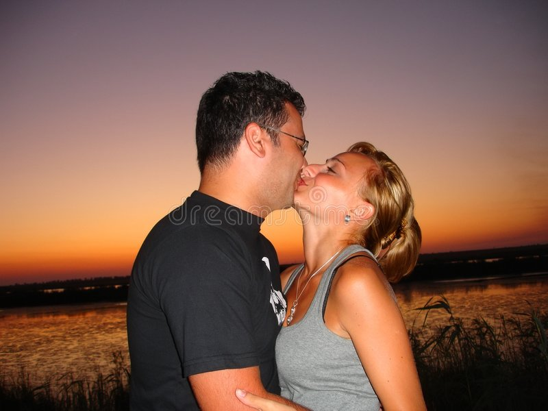 El besarse en la puesta del sol imagen de archivo