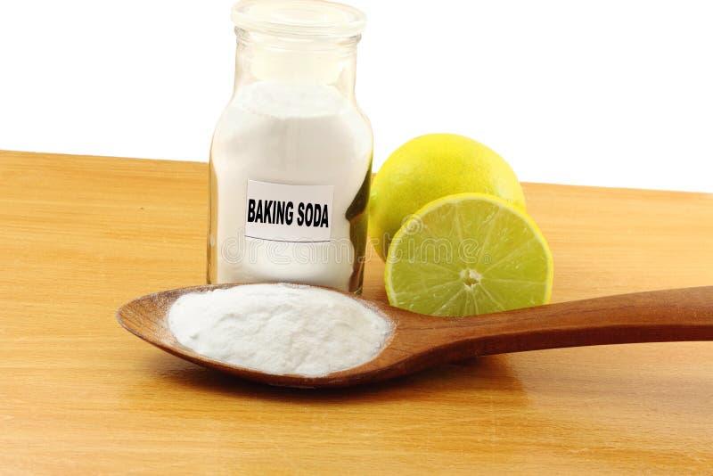 El bicarbonato de sosa en la botella de cristal y la cuchara de madera con el limón dan fruto fotos de archivo libres de regalías