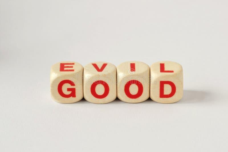 El bien y el mal escrito con los cubos de madera foto de archivo