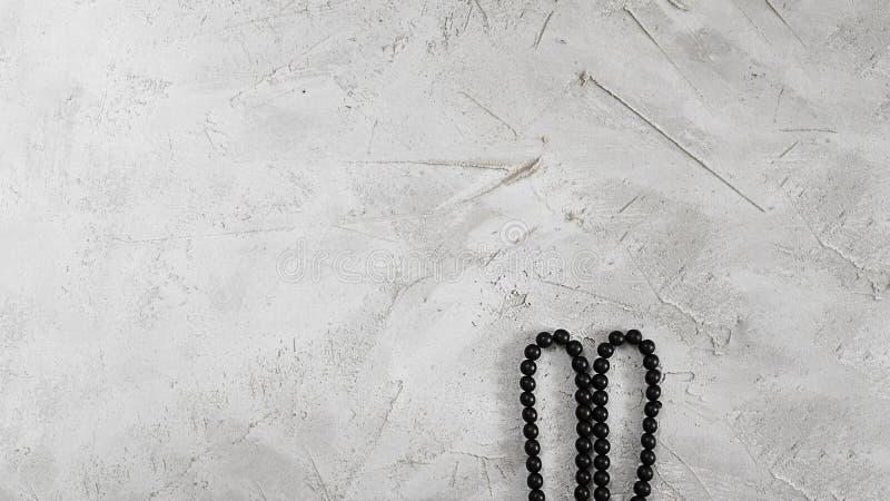 El bijouterie negro gotea el cordón como oídos de conejo en la superficie texturizada gris del cemento, horizontal con el espacio imagen de archivo