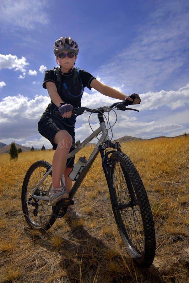 El Biking de la montaña de la mujer joven foto de archivo libre de regalías