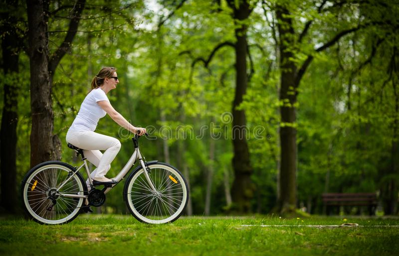 El biking urbano - bici del montar a caballo de la mujer imagen de archivo libre de regalías
