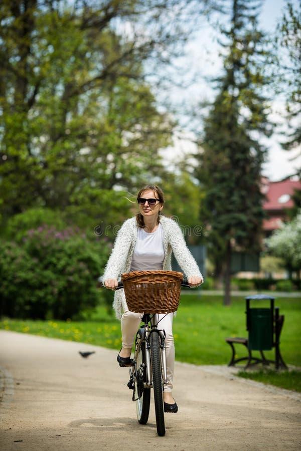 El biking urbano - bici del montar a caballo de la mujer fotos de archivo