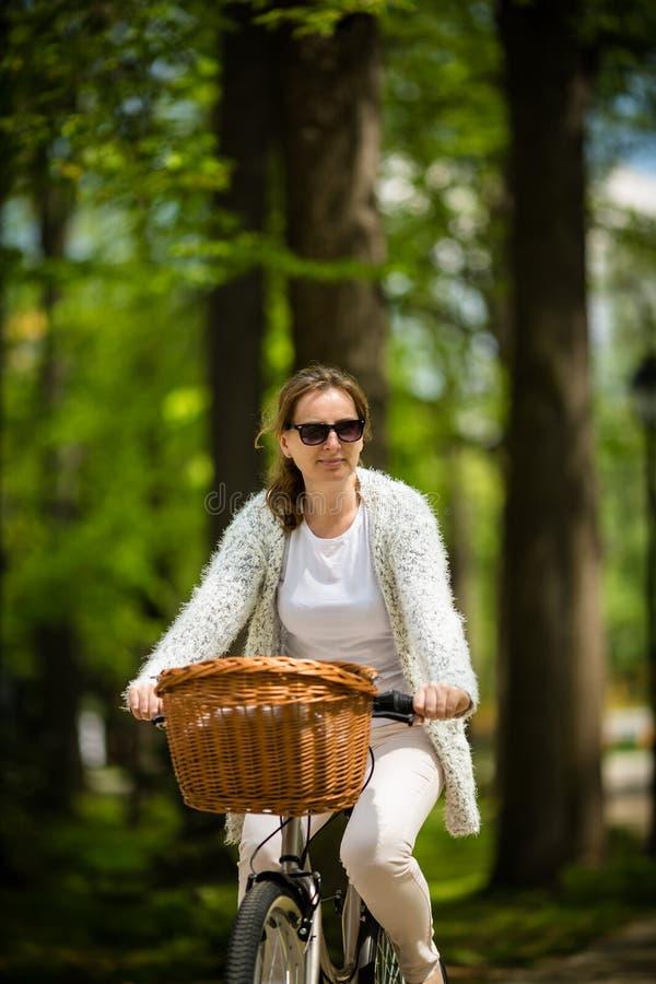 El biking urbano - bici del montar a caballo de la mujer imagen de archivo