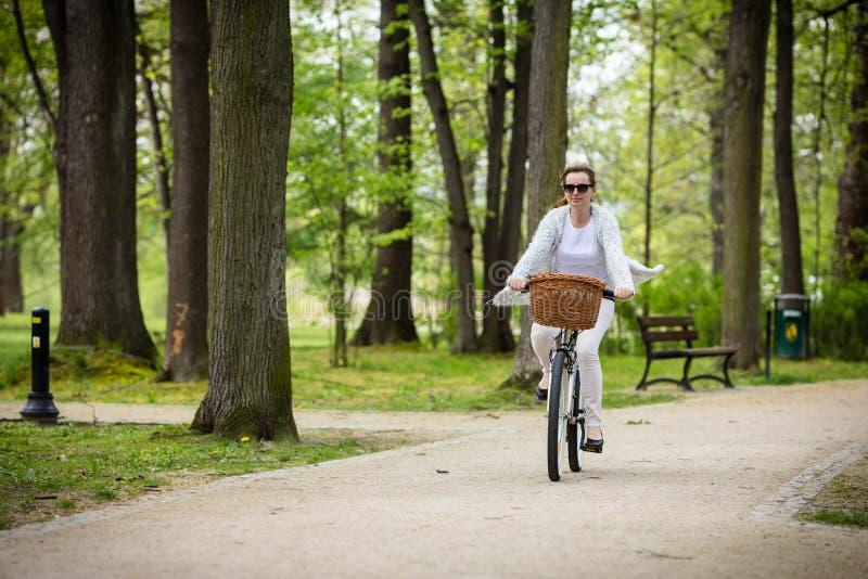 El biking urbano - bici del montar a caballo de la mujer fotografía de archivo