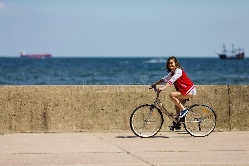 El biking urbano - bici del montar a caballo de la mujer joven imágenes de archivo libres de regalías