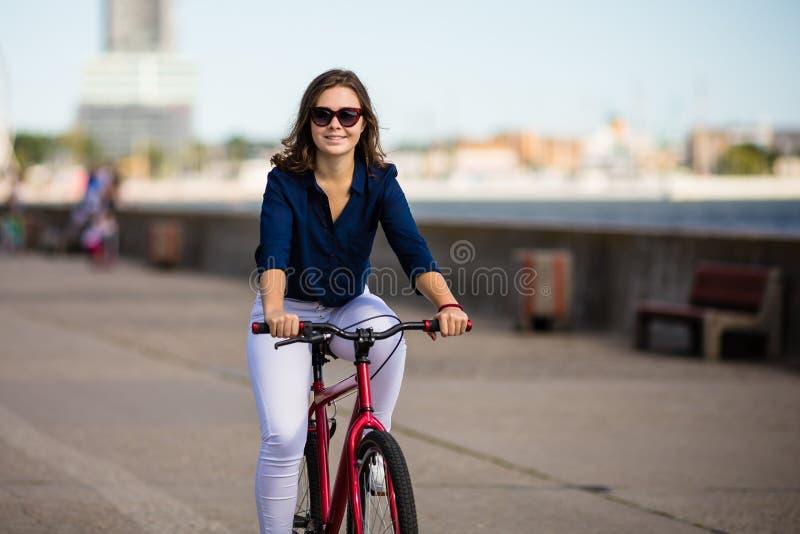 El biking urbano - mujer joven y bici foto de archivo