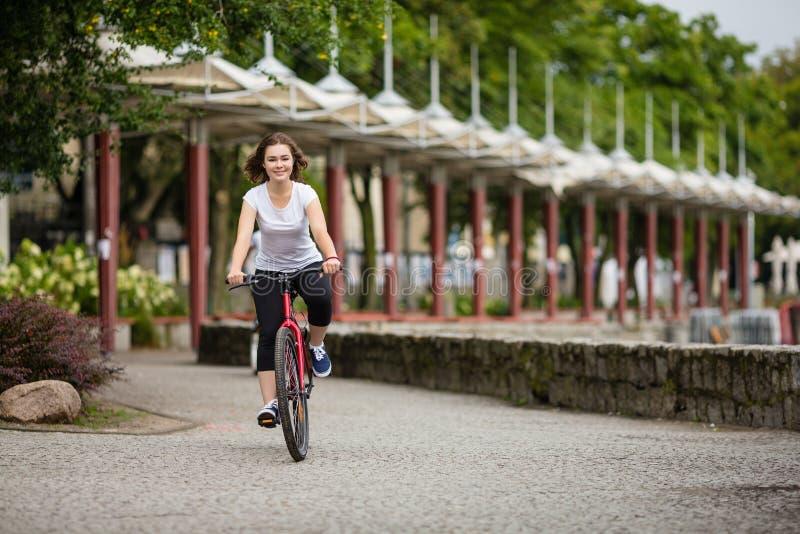El biking urbano - mujer joven y bici en ciudad imagenes de archivo