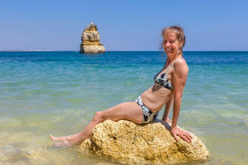 El bikini que lleva de la mujer se sienta en roca en el mar imagen de archivo libre de regalías