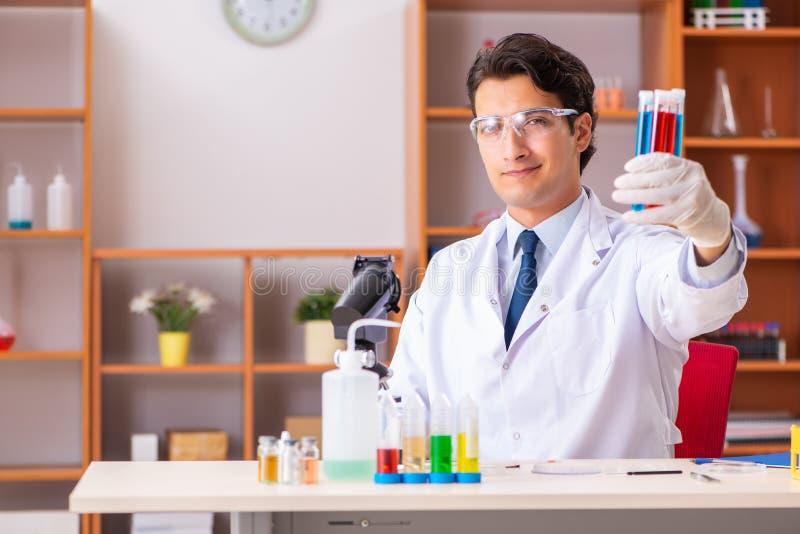 El bioquímico hermoso joven que trabaja en el laboratorio fotografía de archivo