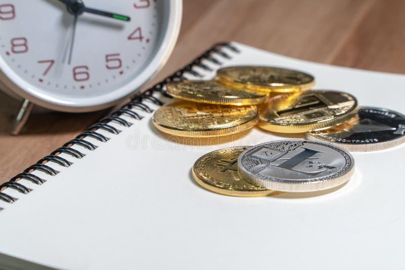 El bitcoin de Cryptocurrency, bitcoin, Litecoin colocó en el cuaderno vacío con el despertador blanco del vintage en la tabla de  foto de archivo