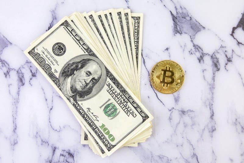 El bitcoin de la moneda de oro miente en un fondo de mármol blanco al lado de un paquete de dólares Intercambio de Cryptocurrency fotografía de archivo libre de regalías