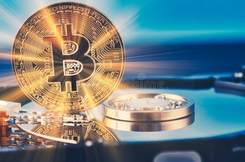 El bitcoin de oro encendido desmonta el disco duro sobre fondo y rayo ligero oscuros suavemente encendidos fotos de archivo