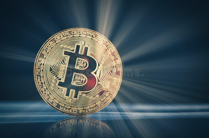 El bitcoin de oro encendido desmonta el disco duro sobre fondo y rayo ligero oscuros suavemente encendidos imagen de archivo