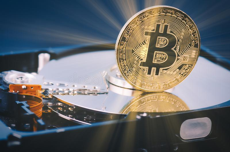El bitcoin de oro encendido desmonta el disco duro sobre fondo y rayo ligero oscuros suavemente encendidos fotografía de archivo