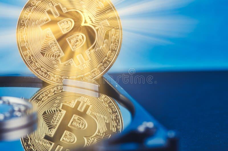 El bitcoin de oro encendido desmonta el disco duro sobre fondo y rayo ligero oscuros suavemente encendidos imagenes de archivo