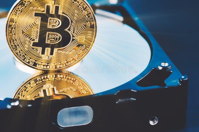 El bitcoin de oro encendido desmonta el disco duro sobre fondo y rayo ligero oscuros suavemente encendidos fotografía de archivo libre de regalías