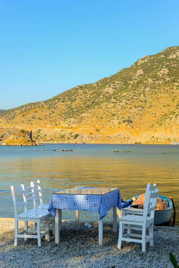 El blanco pintó sillas y la tabla de madera con el mantel modelado flor por la playa en la puesta del sol imágenes de archivo libres de regalías