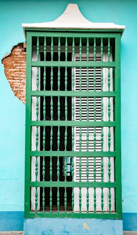 El blanco shuttered la ventana con las barras de madera verdes en la pared azul con fotos de archivo