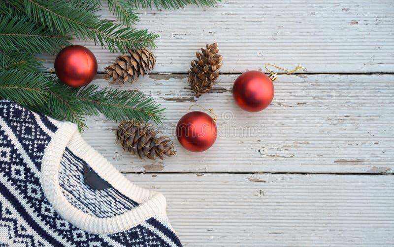 El blanco y el negro hicieron punto el suéter en modelo de la Navidad del invierno en fondo de madera con las ramas del árbol de  fotografía de archivo