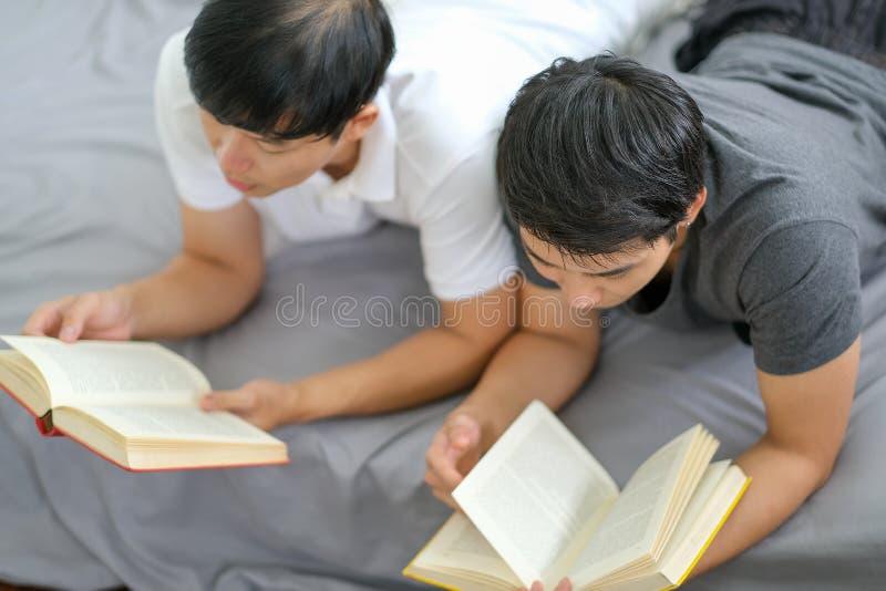 El blando suave de dos tipos leen algunos libros juntos en la cama y parecen disfrutar con la actividad imagen de archivo