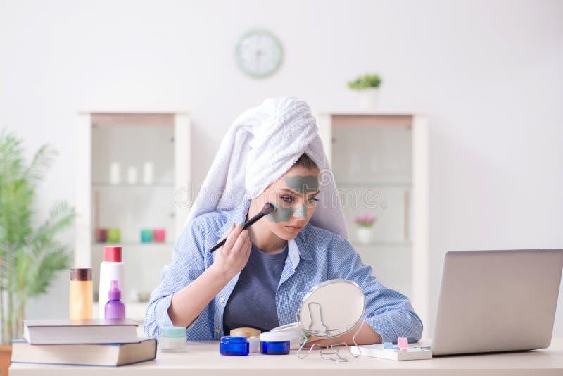 El blogger de la belleza que aplica la máscara y que la fija al blog de Internet imagen de archivo libre de regalías