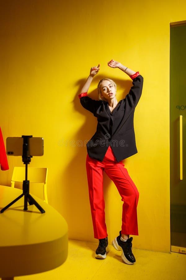 El blogger joven de la muchacha de la moda vestido en pantalones rojos y chaqueta negra toma un selfie en la situaci?n del smartp foto de archivo libre de regalías