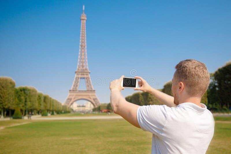 El blogger masculino tira la torre Eiffel en París en el teléfono de las noticias El concepto de turismo, viaje foto de archivo libre de regalías