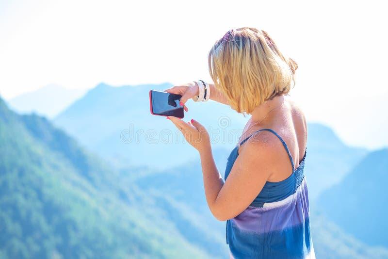 El blogger turístico toma las imágenes del paisaje en su smartphone foto de archivo libre de regalías