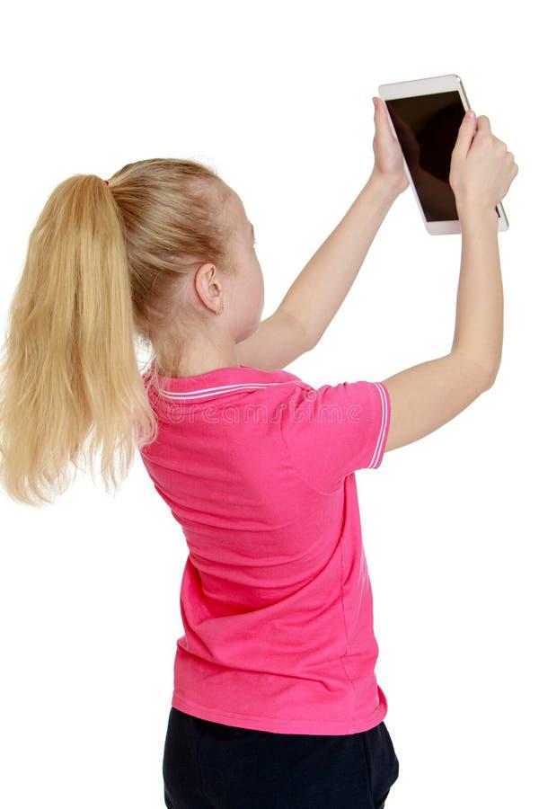 El blonde adolescente mira la pantalla de una tableta imagen de archivo