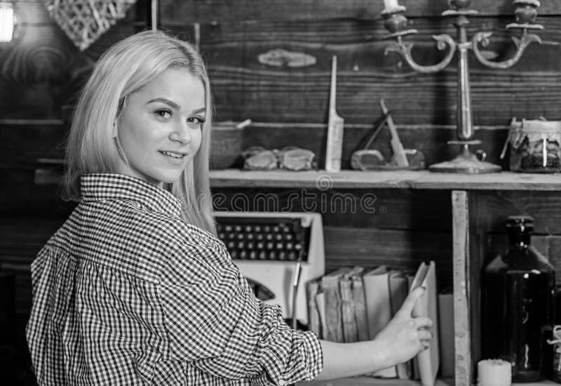 El blonde de la señora en tela escocesa viste tomar el libro del estante Concepto de la biblioteca casera Muchacha que busca el l imagenes de archivo
