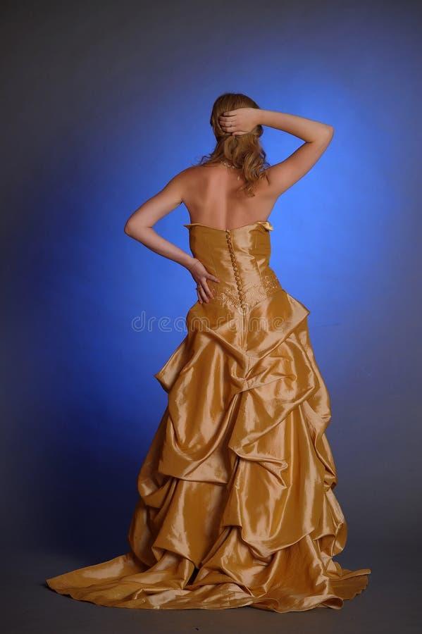 El Blonde en un vestido elegante del oro está detrás en la imagen foto de archivo libre de regalías
