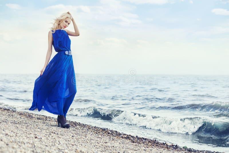 El Blonde en vestido azul camina a lo largo de la 'promenade' por el mar, vacaciones de verano en el mar Retrato sensual hermoso  fotos de archivo