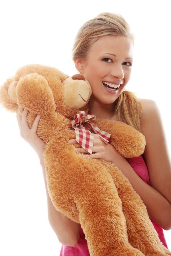 El blonde encantador abraza el oso de peluche   foto de archivo