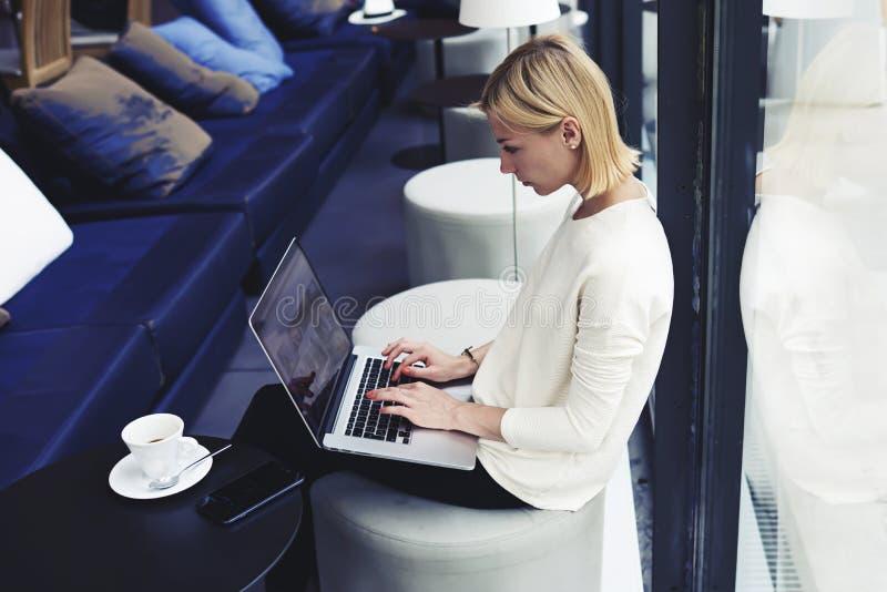 El blonde hermoso con el pelo corto que se sienta en un café en su hora de la almuerzo, correo electrónico de las exploraciones imagen de archivo