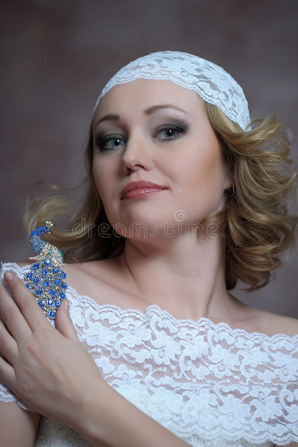 El blonde hermoso con un vestido blanco del cordón foto de archivo