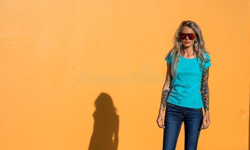El blonde hermoso en gafas de sol mira la cámara Retrato en el fondo de la pared anaranjada brillante Muchacha moderna del inconf imagen de archivo libre de regalías