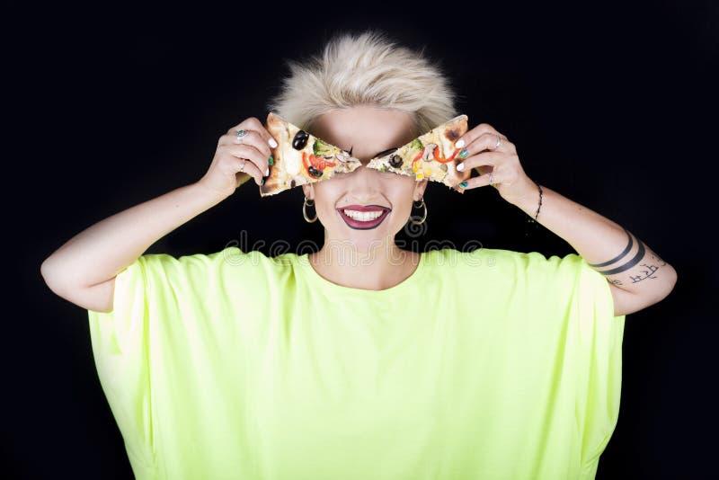 El blonde hermoso en una blusa verde clara con una pizza en Han imagenes de archivo