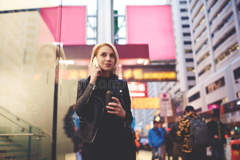 El blonde hermoso joven está viajando por el trabajo que camina en avenida apretada con café imagenes de archivo