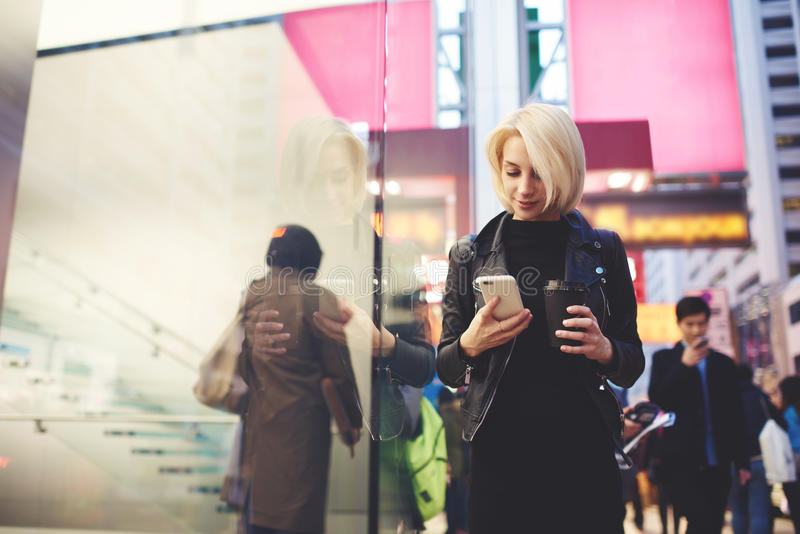 El blonde hermoso joven está viajando por el trabajo que camina en la calle usando Internet 4G fotografía de archivo libre de regalías