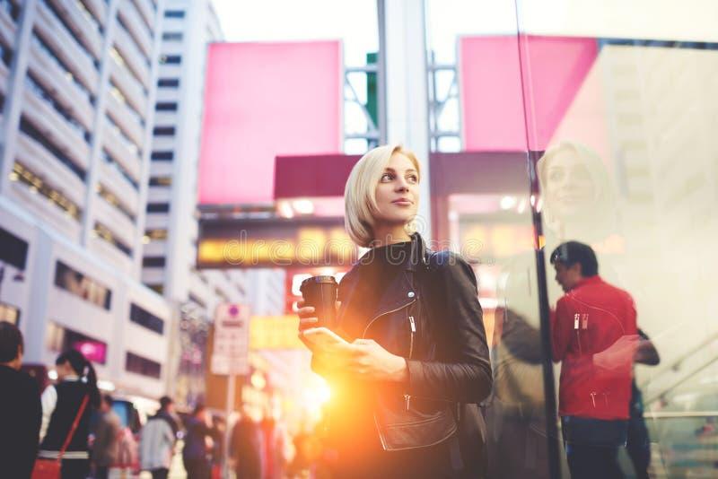 El blonde hermoso joven está viajando por el trabajo que se coloca al aire libre usando el café de consumición del wifi libre par imagen de archivo