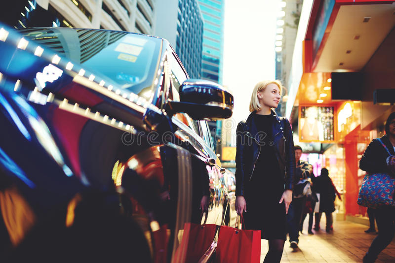 El blonde hermoso joven está viajando por los amigos que esperan del trabajo para que se colocan al aire libre cerca del automóvi foto de archivo libre de regalías
