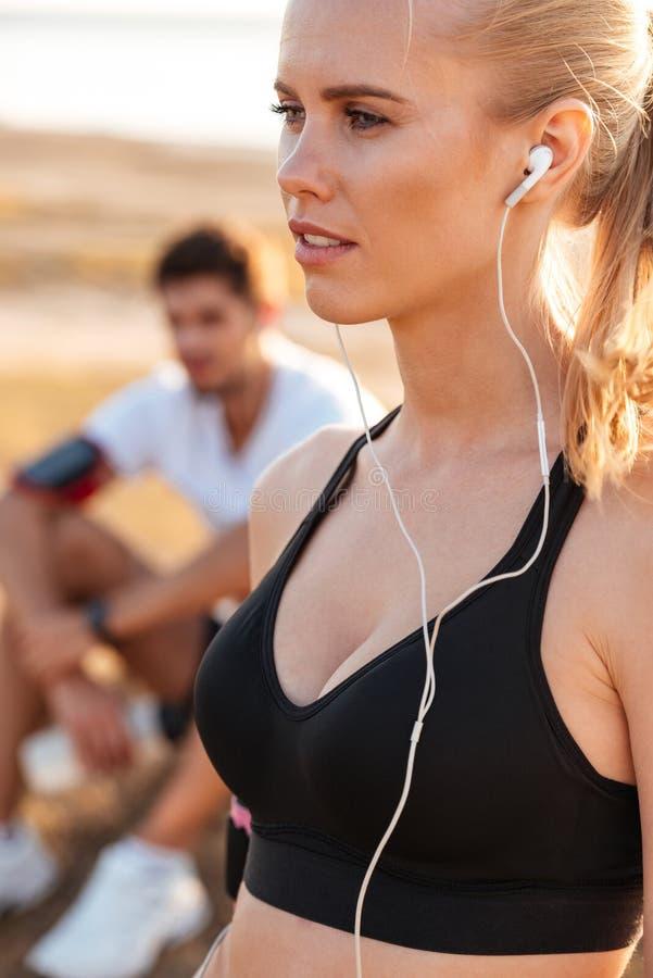 El blonde joven hermoso se divierte a la mujer con los auriculares imagen de archivo