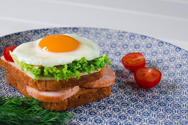 El bocadillo con el huevo, el jamón, el queso, la tostada y la ensalada deja mentiras en una placa con el tomate y el eneldo fotografía de archivo
