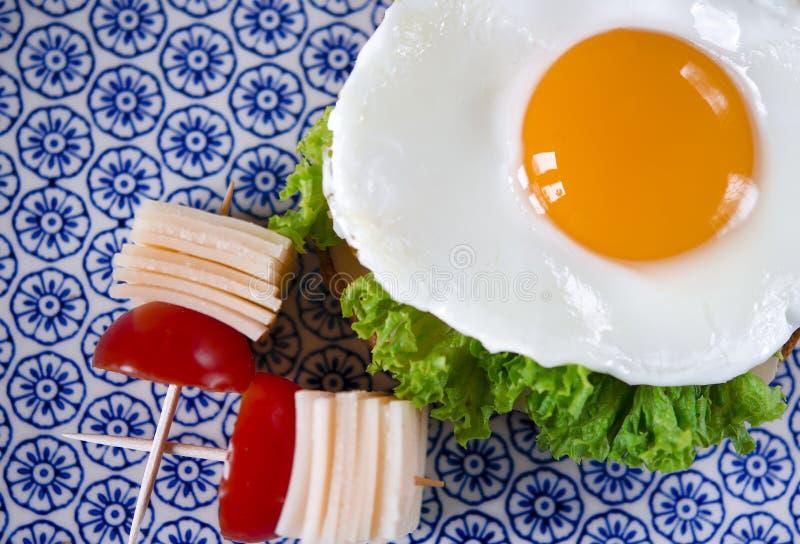 El bocadillo con el huevo, el jamón, el queso, la tostada y la ensalada deja mentiras en una placa con el tomate y el eneldo foto de archivo