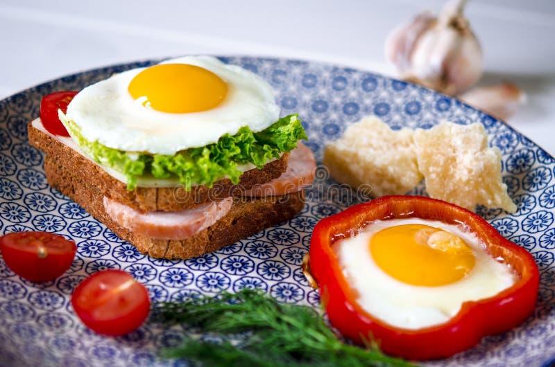 El bocadillo con el huevo, el jamón, el queso, la tostada y la ensalada deja mentiras en una placa con el tomate y el eneldo fotografía de archivo libre de regalías