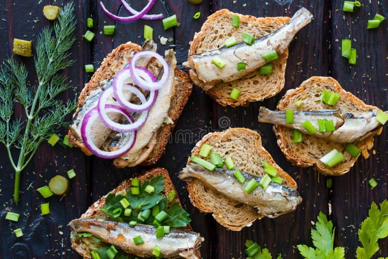 El bocadillo con las sardinas, asperja con las cebollas en un fondo negro imagen de archivo