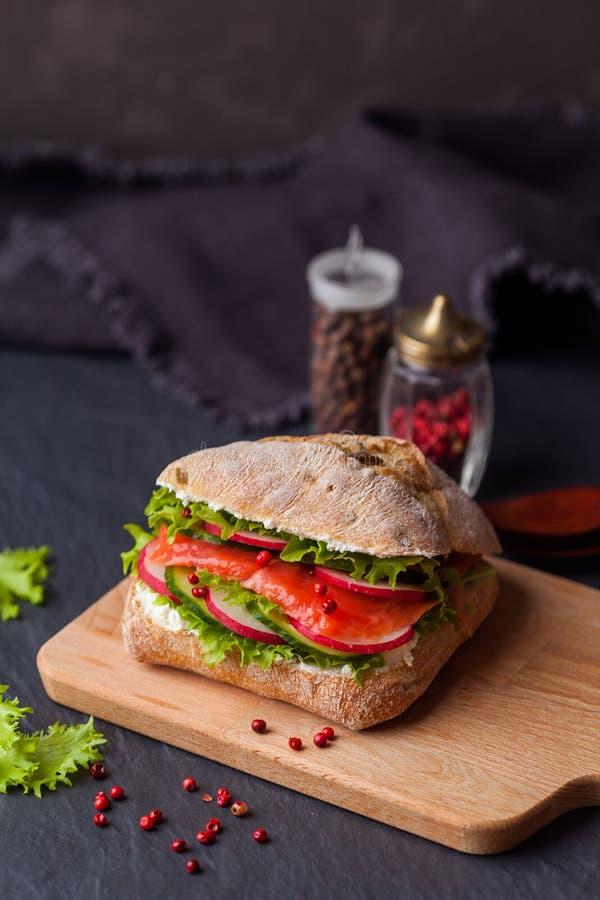 El bocadillo de Ciabatta con los salmones, las verduras y la ensalada fresca encendido cortejan fotos de archivo libres de regalías